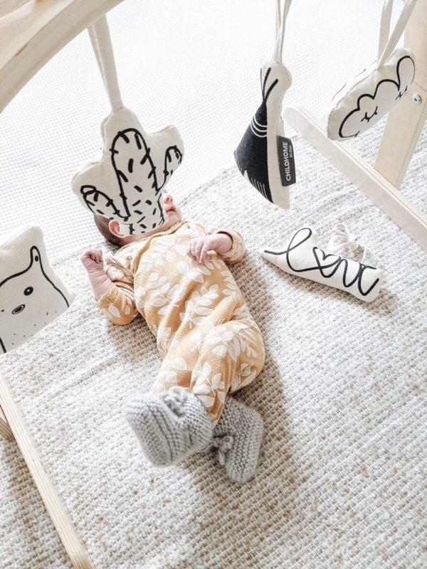 bébé sous portique d'éveil et jouets à suspendre